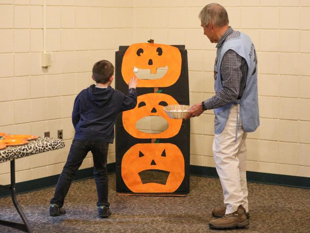 Young boy playing a toss game at Boo at the Zoo
