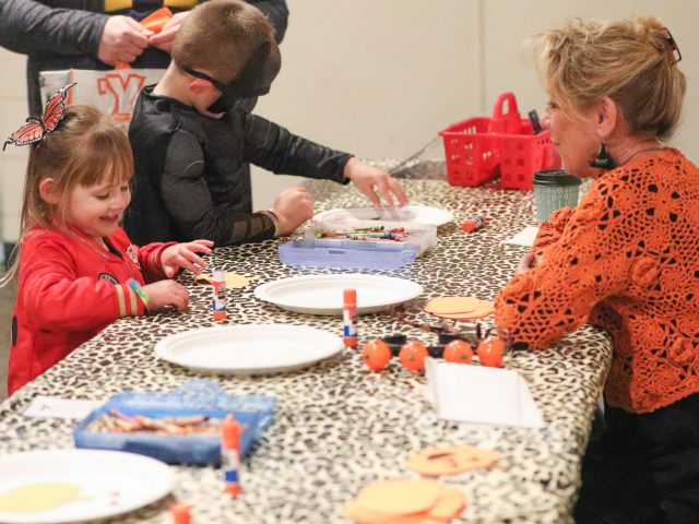 Young girls and boy working on craft projects at Boo at the Zoo